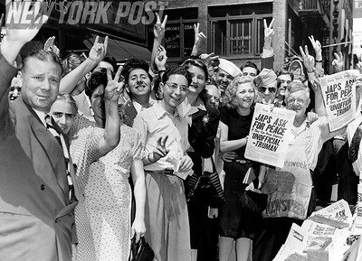 NYC Crowd celebrates Japan's surrender by buying a copy of the New York Post and showing their peace signs. 1945