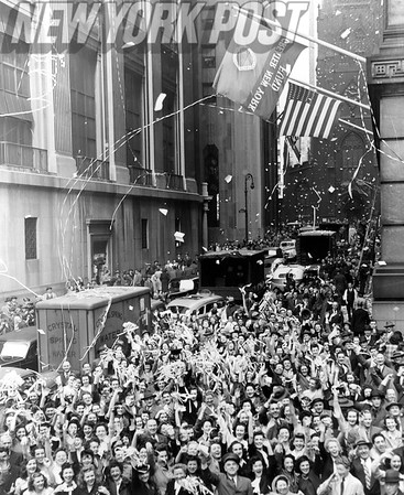 Ticker tape celebration over Germany's World War II surrender at the corner of Wall and Broad Streets.