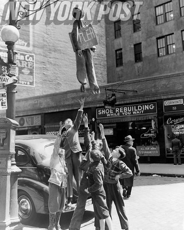 V-E Day This group of boys try to grab an effigy of Adolf Hitler at the corner of Greenwich & Liberty Streets. 1945
