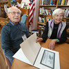 Al Sidel, 92, of Chelmsford, with Veronica Doherty, 85, also of Chelmsford, who has on a volunteer basis been writing down life stories of the Greatest Generation and creating booklets for them and their families. Sidel's booklet includes this picture of the aircraft carrier USS Bunker Hill, on which Sidel, a Navy shipfitter, survived a kamikaze attack by two Japanese planes in which two friends who went to get a snack were among 500 killed. (SUN/Julia Malakie)