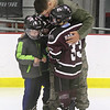 Airman Steven Lubinger, 18, of Chelmsford, surprises his younger brothers , from left, Gabe, 7, Ben, 8, and Cam Panzeri, 9, at Cam's Squirt 1 hockey game at Breakaway Ice Center. (SUN/Julia Malakie)