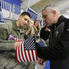Airman Steven Lubinger, 18, of Chelmsford, receives a gift from rink general manager David Hughes of Peabody after surprising his younger brothers at hockey game at Breakaway Ice Center. At right are his girlfriend Jordyn Wright, 17, of Townsend, and his mother Kubryn Panzeri of Chelmsford. (SUN/Julia Malakie)