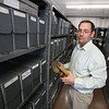 Military archives supervisor Keith Vezeau shows some of the historical materials currently stored in the Concord Armory, which will be moved to the state archives in Dorchester later this year. (SUN/Julia Malakie)