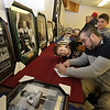 """""""2018 Contribute to the Troops"""" at Lowell VFW Post 662. Bryan Descoteaux of Tewksbury puts in a bid on an autographed photo of Larry Bird. At left is his son Aiden Descoteaux, 10, and at rear, Aiden's cousin Treyvon Pagan, 9, of Lowell.  (SUN/Julia Malakie)"""