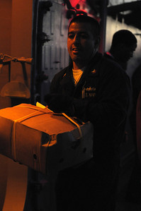 091212-N-0260R-127 - GULF OF ADEN (Dec. 12, 2009) - A Sailor passes boxes of food down the line during an underway replenishment (UNREP) with USNS Kanawha.  Chosin is the flagship of Combined Joint Task Force 151, a multinational task force established to conduct counter-piracy operations under a mission-based mandate to actively deter, disrupt, and suppress piracy off the coast of Somalia. (U.S. Navy photo by Mass Communication Specialist 1st Class Brandon Raile/Released)