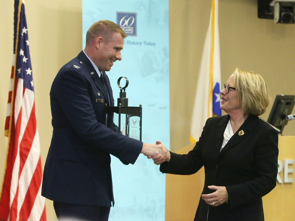 . Retiring U.S. Rep. Niki Tsongas is honored by the regional defense community, at a reception at MITRE in Bedford. Col. Chad Ellsworth, installation commander at Hanscom AFB, presents Tsongas with a replica Paul Revere Old North Church lantern. (SUN/Julia Malakie)