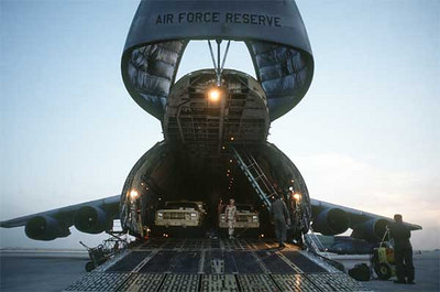 Military trucks are unloaded from the nose ramp of a C-5A Galaxy transport aircraft of the U.S. Air Force Reserve, Military Airlift Command, in support of Operation Desert Shield.