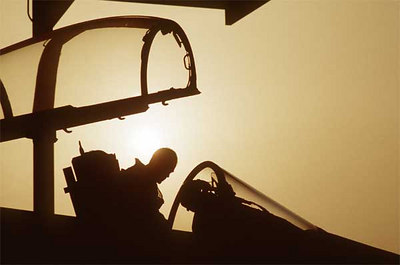 The pilot of a 1st Tactical Fighter Squadron F-15C Eagle aircraft is silhouetted against the sun as he climbs into the cockpit of his aircraft during Operation Desert Shield.