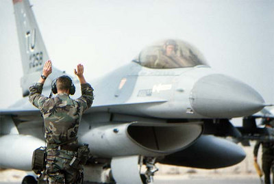 A ground crew member signals to the pilot of a 614th Tactical Fighter Squadron F-16C Fighting Falcon aircraft as it prepares to takeoff on the first daylight strike against Iraqi targets during Operation Desert Storm.