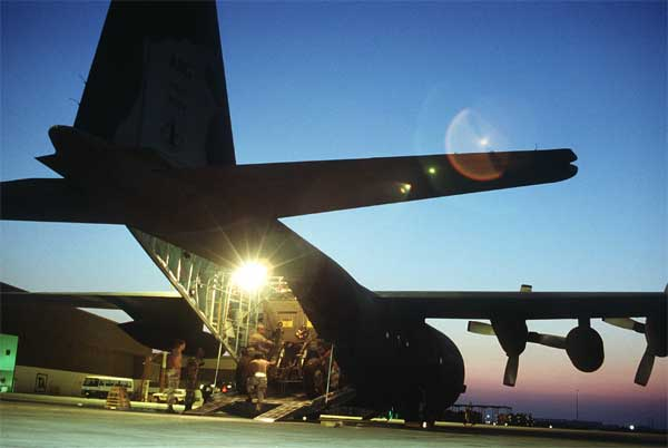 A crew of the 181st Tactical Airlift Squadron, Texas Air National Guard, load equipment of the 435th Airlift Control Element onto a C-130 Hercules transport aircraft during Operation Desert Shield.