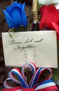 """Silk roses and a ribbon hold a handwritten note, saying """"Gone but not Forgotten,"""" at the 14th Quartermaster Detachment Memorial at the Army Reserve center in Greensburg, Pa."""