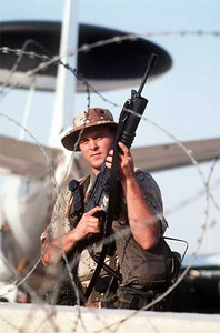 An Airman 1st Class armed with an M-16A1 rifle equipped with an M-203 grenade launcher stands guard near an E-3A Sentry aircraft during Operation Desert Shield.