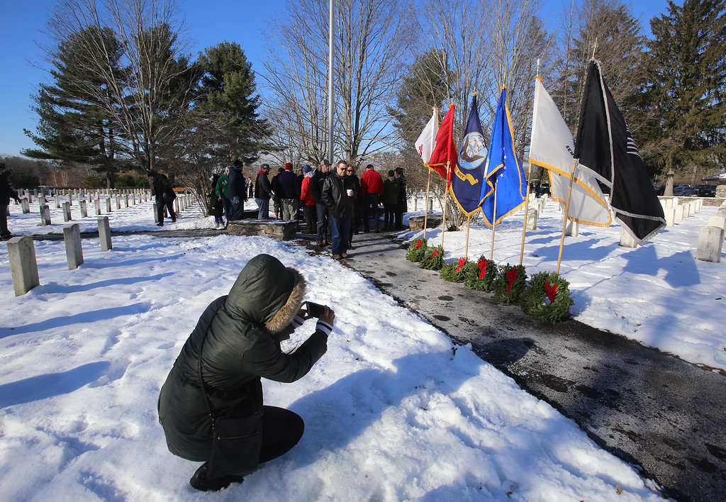 . Wreaths Across America ceremony at Fort Devens Cemetery, where volunteers laid wreaths on 432 veterans\' graves. US Army SGT Sonya Morand of Framingham takes a picture of the wreaths for each service branch, after the ceremony. (SUN/Julia Malakie)