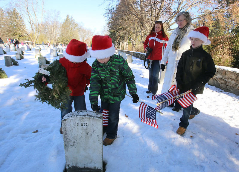 Wreaths Across America ceremony at Fort Devens Cemetery, where volunteers laid wreaths on 432 veterans' graves. Brothers, from left, Logan, 6, Evan, 7, and Dylan Gibbons, 9, help lay wreaths with their mother Sarah Gibbons and her mother Karen Januskiewicz. All are from Ayer. (SUN/Julia Malakie)