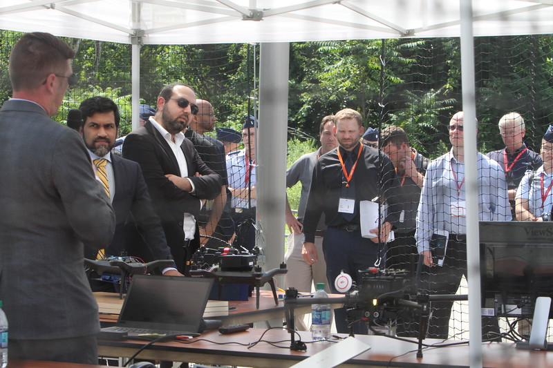 Viewers watch from outside the Drone Cage, demonstrations with drones at Air Force UAS Pitch Day, at Northeastern University's Innovation Campus.  (SUN/Julia Malakie)