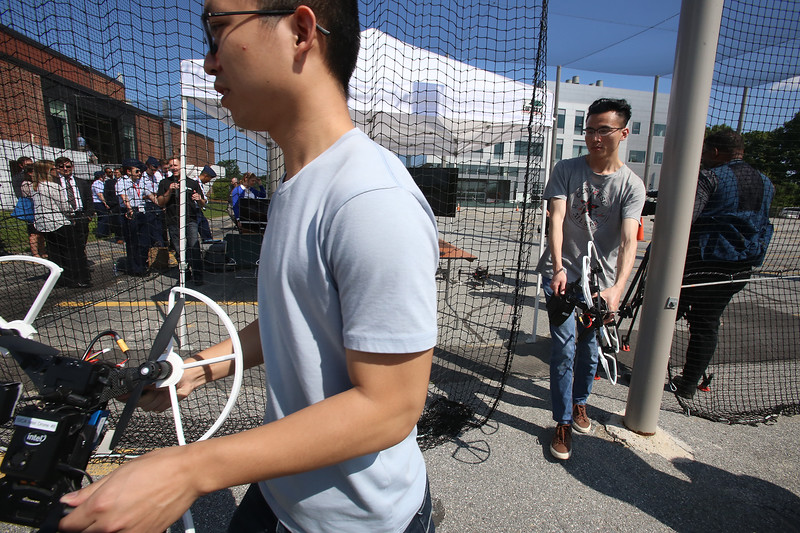 Demonstrations with drones at Air Force UAS Pitch Day, at Northeastern University's Innovation Campus. NU PhD students Zixuan Liang, left, and Weite Zhang, both from China and now of Boston, carry out drones after a demonstration of swarm tracking, which happened in NU's 150ft x 200ft x 62ft tall Drone Cage. (SUN/Julia Malakie)