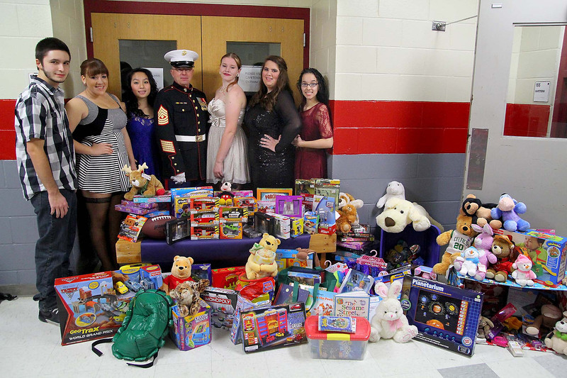 """The student coordinators of the Fitchburg High School """"Winter Ball""""  committee stand  behind the toys they collected for the Toys for Tots program with Marine First SGT. Mike Sabor a commandant with the Marine Corp League. From left is senior Athan Hristodulu, senior Alaza Merrill, freshman Judy Duong, senior Mary-Kate Myers, junior Hallie Newcombe and junior Skylyn Torres. They collected over 200 toys with 100 dollars from the dance money and $200 from the teachers going to purchase many of the toys. If the kids brought in a toy they got half off their ticket. SENTINEL & ENTERPRISE/ JOHN LOVE"""