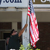 LAER Realty holds a Flag Take Down celebration and fundraiser for Massachusetts Fallen Heroes, to take down about 700 American flags to reuse next year. Mike Kendrick of Chelmsford puts up a large flag as Taps is played. (SUN/Julia Malakie)