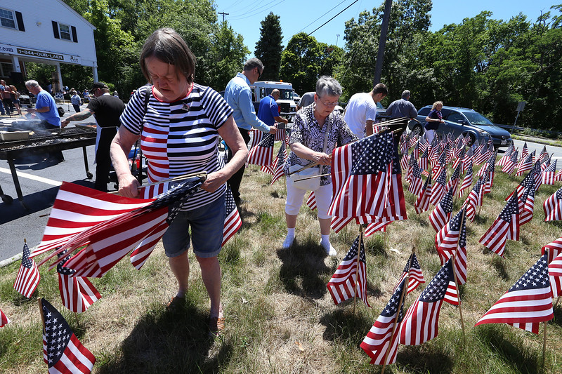 LAER Realty holds a Flag Take Down celebration and fundraiser for Massachusetts Fallen Heroes, to take down about 700 American flags to reuse next year. Nancy Pittman, left, and Pat DeFreitas, both of Chelmsford, help pull up flags. (SUN/Julia Malakie)