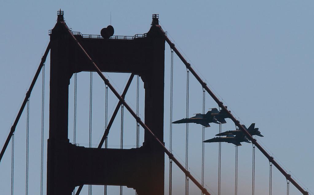 The Blue Angels fly behind the Golden Gate Bridge during Fleet week in San Francisco, Calif., on Saturday, October 8, 2011.