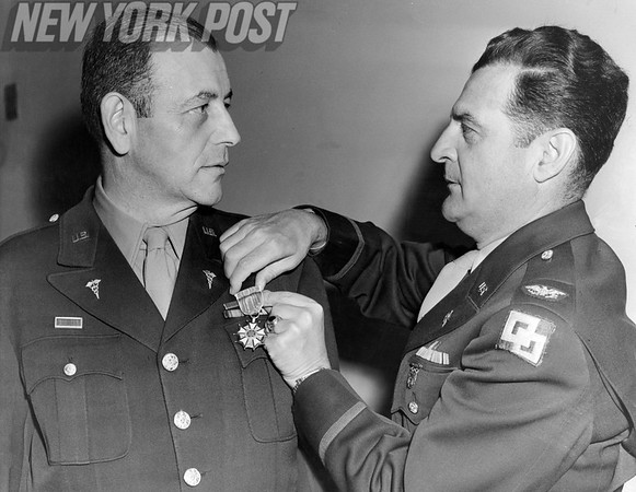 Col. Julius M. Blank received the Legion of Merit medal from Col. Edward C. Miller. 1945