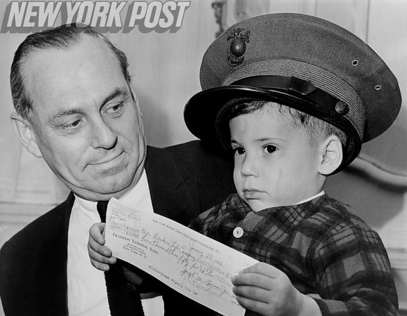 Brig. Gen. Marlin F. Rockmore presents a scholarship to orphaned child Andrew Gagliardo when his father was killed in action in Vietnam. 1966