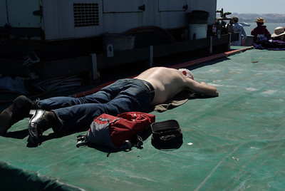 TOO MUCH FUN  -- After a day of 'brews for the crew'  an old timer catches a brief nap on a hatch cover on the return trip.