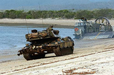 An Australian Army Leopard AS1 main battle tank moves up the beach after being transported ashore by a U.S. Navy Landing Craft, Air Cushion (LCAC).