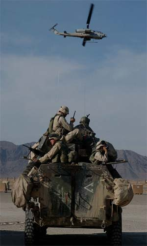 """Marines on a Light Armored Vehicle (LAV) prepare to go on patrol as an AH1W """"Super Cobra"""" helicopter flies by."""