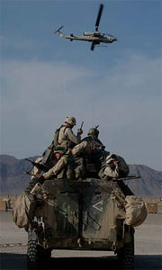 "Marines on a Light Armored Vehicle (LAV) prepare to go on patrol as an AH1W ""Super Cobra"" helicopter flies by."