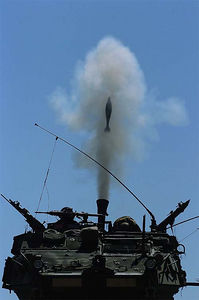 A 120mm mortar round sails out of the tube of a Stryker MCV-B