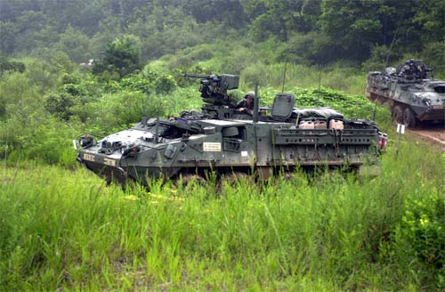Stryker infantry carrier vehicles speed out of the woodline toward their firing positions.