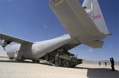 A Stryker Mortar Carrier exits the tail of an Air Force C130 Hercules aircraft.