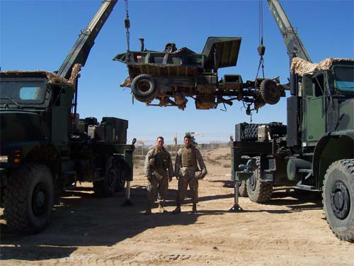 Marines pose between two wreckers suspending a piece of recovered equipment in the air.