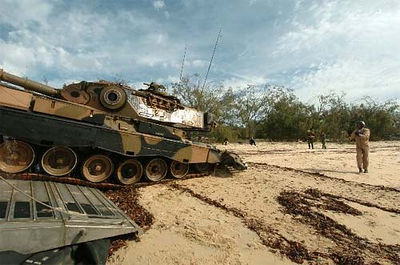 An Australian Army Leopard AS1 main battle tank is directed onto the beach.