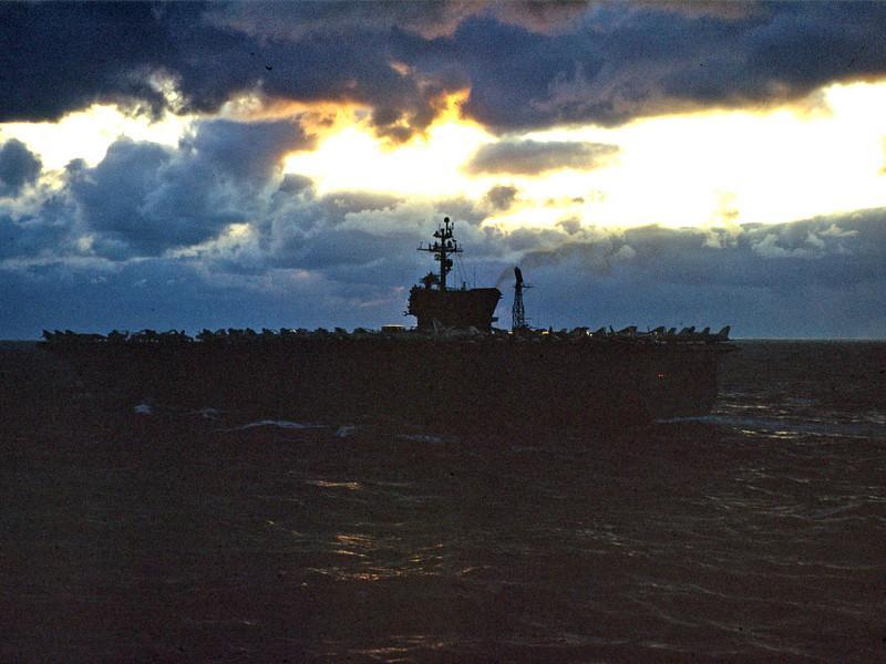 USS John F Kennedy at dusk as HMS Hermes steams past. c.10 Oct 1973
