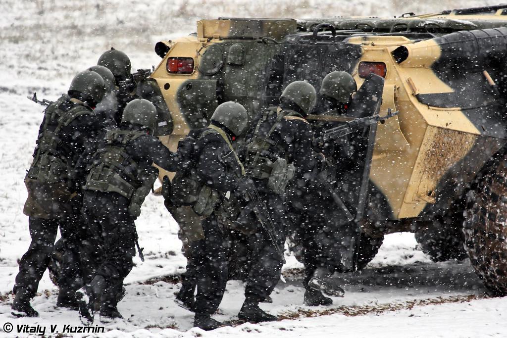 За ним следует штурмовая группа военнослужащих 604 Центра специального назначения ВВ МВД России (Assault group from Internal troops 604 Special purpose center (former Vityaz and Rus' units) under cover by BTR-80)