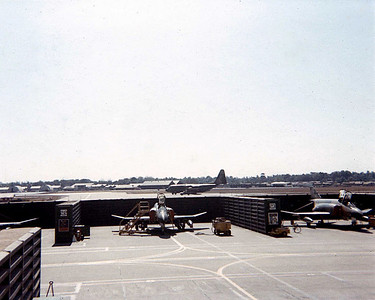 F4s parked in revetment C-130 in background.