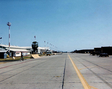 Flight line bomb delivery trailers to the right various shops to the left.