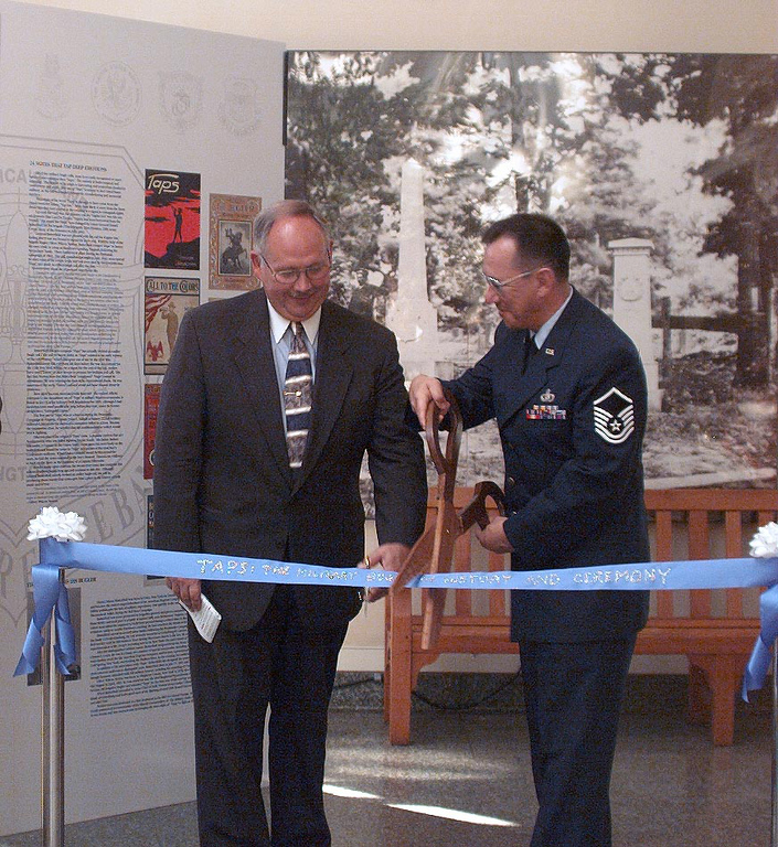 Mr. Jack Metzler, superintendent of Arlington and Master Sgt. Jari Villanueva, creator of the Taps Exhibit, prepare to cut the ribbon, officially opening the display.  (photo by SSgt Joan D. Anderson-Brown)