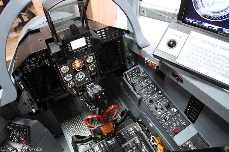 Процедурный тренажер МиГ-29СМТ. Предназначен для ознакомления пилота с интерьером кабины МиГ-29СМТ, формирования навыков деятельности экипажа в кабине и работы с ее информационно-управляющим полем, привития навыков действий по управлению силовой установкой, самолетными системами и оборудованием, использованию комплекса бортового оборудования в ходе подготовки к полету и выполнения полетного задания. (MiG-29SMT procedure training simulator)
