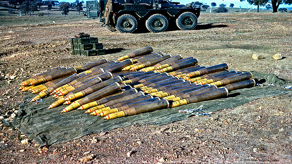 High explosive 20 pounder rounds for our Centurian tanks at Puckapunyal in Victoria. Snowy Davies Saladin 6WD APC in the background.  Note boxes of .30 ammo belts for our Browning machine guns on the tank. Us gunners flick a lever one way to fire machine gun, other way for the main gun. Each round was worth more than this soldier's pay. Accurate gunnery starts with bore sighting the gun with a cotton cross, then shooting it in to set the sight. After that ! Look out.