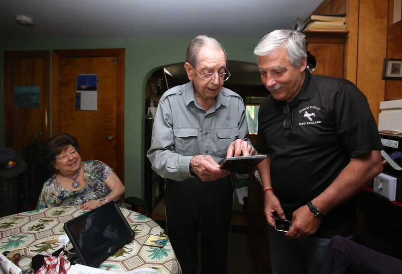 WWII Army veteran Henry Naruszewicz, 103, of Lowell, talks with Honor Flight New England founder Joe Byron of Manchester, N.H., about his WWII expereriences. At left is his daughter Dorothy Flanagan, also of Lowell. (SUN/Julia Malakie)