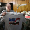 WWII Army veteran Henry Naruszewicz, 103, of Lowell, holds up a tee shirt he was given for an upcoming Honor Flight trip to Washington, DC. But he plans to wear a regular shirt so he'll have pockets. (SUN/Julia Malakie)