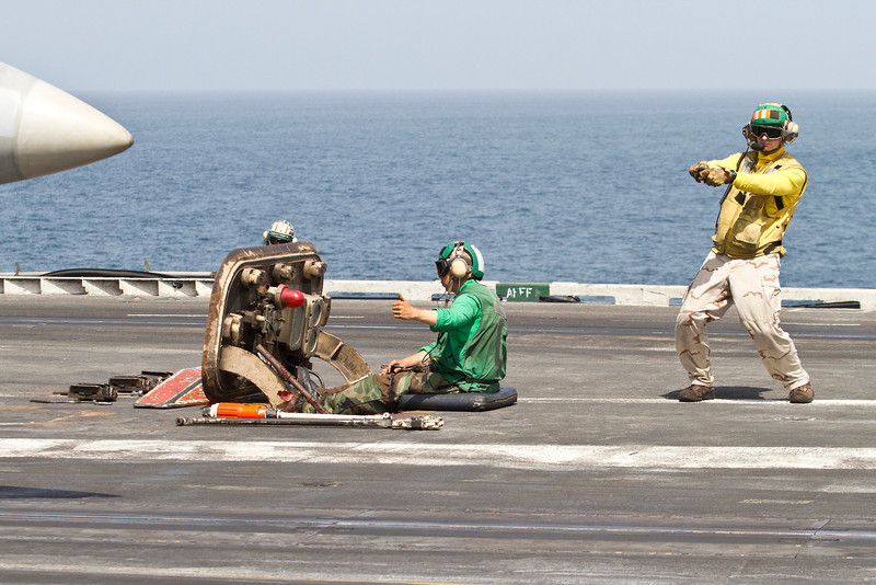 August 29, 2012-Undisclosed ship at sea. National Cartoonists Society members, Jeff Bacon, Dave Coverly, Jeff Keane, Rick Kirkman, Tom Richmond and Sam Viviano visit with military personell and boost their morale by talking with them and drawing cartoons and caracatures for them. Aircraft handler directs pilot in preparation for a catapult launch.