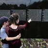 The Moving Wall Vietnam Veterans Memorial is set up on Wilmington Common. Aiden Tumlin, 7, of Wilmington, and his friend Tess Sullivan, 8, of Wilmington, look for last names they recognize. They didn't know specific people -- they were just spotting familiar last names. (SUN/Julia Malakie)