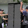 The Moving Wall Vietnam Veterans Memorial is set up on Wilmington Common. Henry Diorio of Wilmington, front left, helps assemble the wall. (SUN/Julia Malakie)