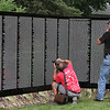 The Moving Wall Vietnam Veterans Memorial is set up on Wilmington Common. Tony Attardo of Hudson, N.H., left, takes photos of the partially assembled wall. (SUN/Julia Malakie) [NOTE: man at left didn't want to give name.]