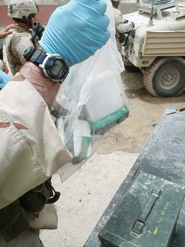 SSG Mark Palmer bags a bomb trigger, so forensic analysts in Baghdad and at FBI headquarters in Virginia can examine it.