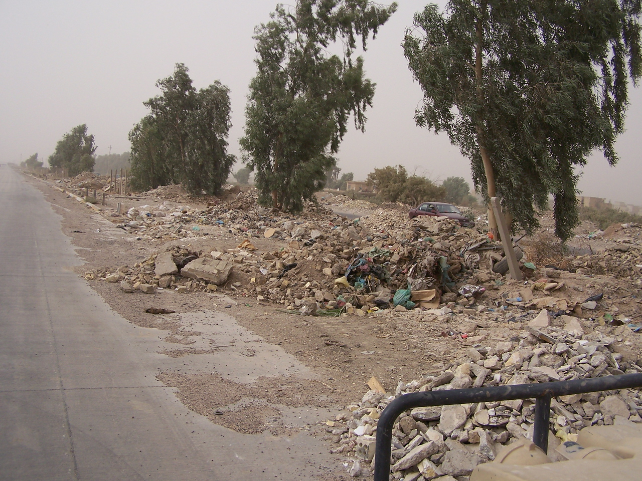 The streets of Baghdad are lined with rubble and trash.  A bomb could be hidden anywhere.